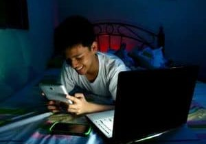 Young-lad-using-a-smart-phone-and-a-laptop